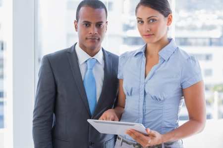 Business team with tablet pc looking at camera in the office Stock Photo - 20591544