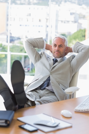 Businessman relaxing at his desk in the office photo