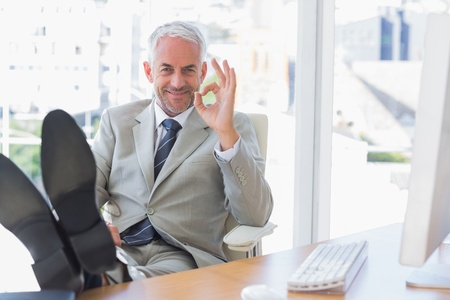 Happy businessman giving ok sign with feet up on his desk photo