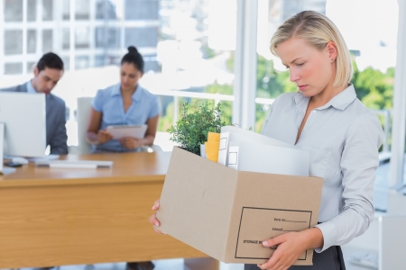 unemployed dismissed: Businesswoman leaving office after being laid off carrying box of belongings Stock Photo