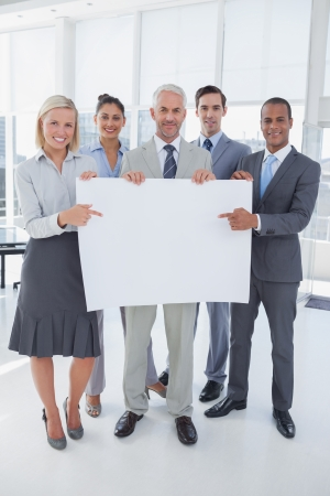Business team holding large blank poster and smiling at camera in bright office photo