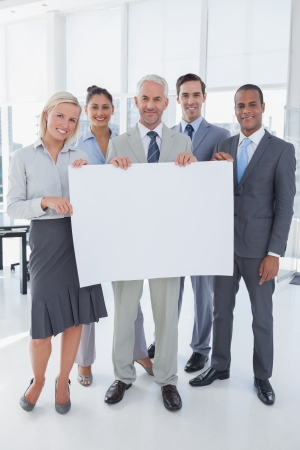 Happy business team holding large blank poster and looking at camera photo