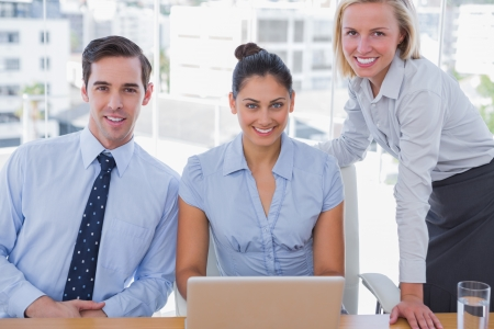 Business team with laptop smiling at camera at desk in office photo