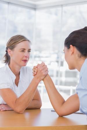 Rival businesswomen having an arm wrestle in their office photo