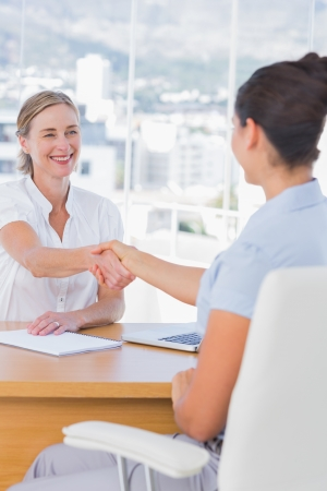 Handshake business: Cheerful interviewer shaking hand of an applicant in her office Stock Photo