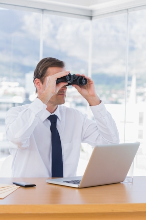 foresight: Businessman using binoculars while he is working in his office Stock Photo