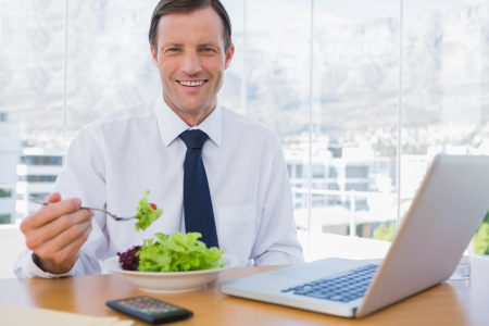 Happy businessman eating a salad on his desk during the lunch time