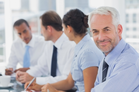 Boardroom meeting: Smiling businessman posing in the meeting room with colleagues working next to him
