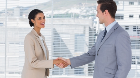 Businesswoman shaking hands to businessman in the office photo