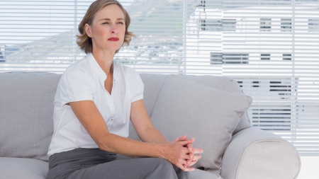 Serious businesswoman sitting on couch and looking away photo