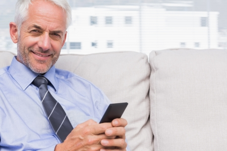 Happy businessman using smartphone on couch in staffroom photo