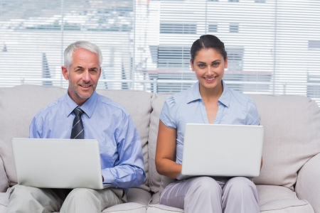 Business people sitting on sofa using their laptops and smiling at camera in staffroom photo