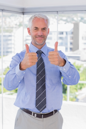 man thumbs up: Businessman smiling with thumbs up at camera in his office