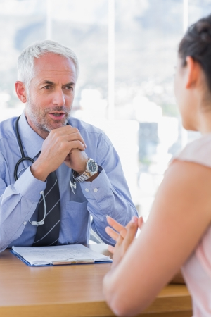 female doctor: Doctor talking to patient in his office