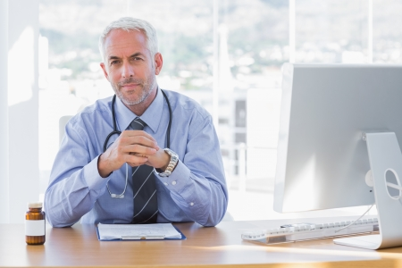 Serious doctor sitting at his desk and looking at camera photo