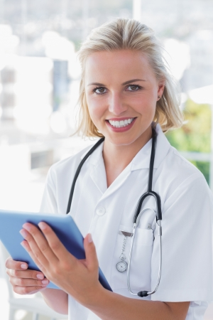 Portrait of a cheerful nurse holding a digital tablet photo