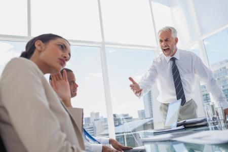jefe enojado: Protuberancia furiosa gritando a sus colegas durante una reuni�n