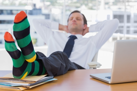 Businessman sleeping with feet without shoes on his desk