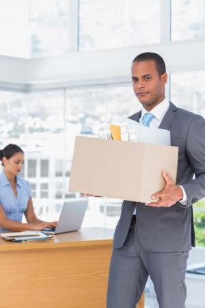 Upset businessman leaving the company while holding a box with his stuff photo