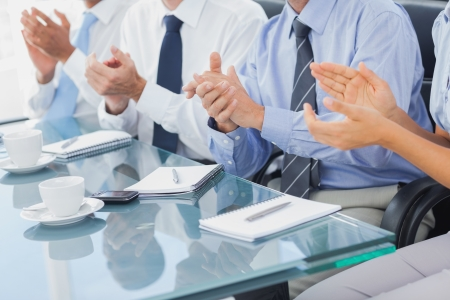 Boardroom meeting: Group of business people applauding in the boardroom during a meeting