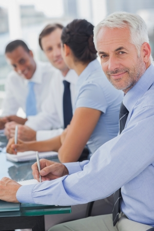 young man portrait: Cheerful businessman posing in the meeting room while colleagues are working behind Stock Photo