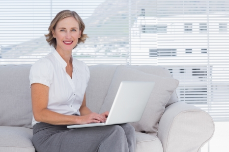 Businesswoman with laptop sitting on couch photo