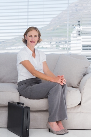 Businesswoman sitting on couch waiting in a waiting room photo