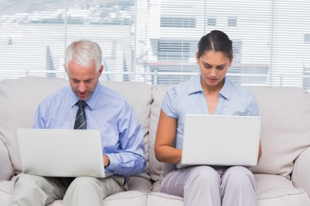 Business people sitting on sofa using their laptops in staffroom