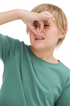 stench: Boy pinching his nose on white background  Stock Photo