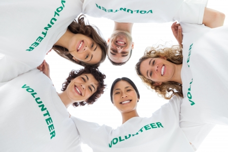altruism: Ángulo de visión baja de personas que llevan voluntarios camiseta sobre fondo blanco Foto de archivo