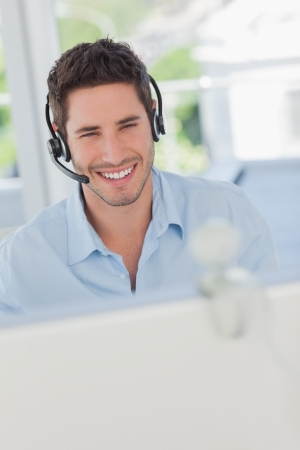 Cheerful designer with a headset having a video chat in his office  photo
