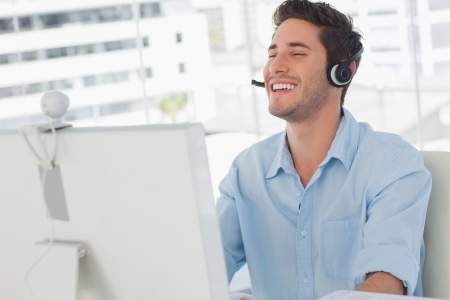 webcam: Happy designer laughing during an online communication in his office Stock Photo