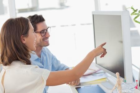 work together: Aantrekkelijke foto-editor wijst op het scherm tijdens het werken met een collega