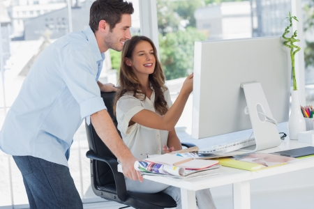 Two photo editors working on a computer in their office Stock Photo - 20591484
