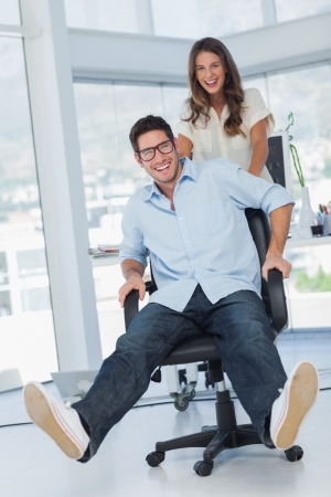 Happy designers having fun with a swivel chair in their office photo