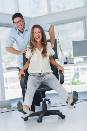 Cheerful designers having fun with a swivel chair in their office photo