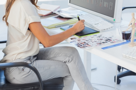 Photo editor pointing using graphics tablet in her office photo
