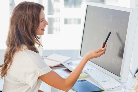 Pretty photo editor pointing at the screen in her office photo
