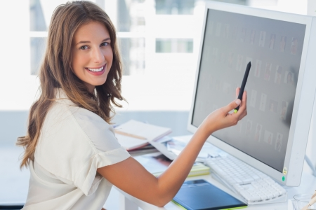 Attractive photo editor pointing at the screen in her office photo