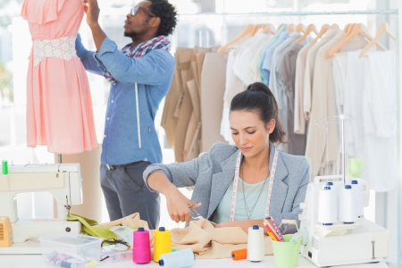 fashion clothing: Fashion designer cutting textile at desk while her colleague adjusting dress behind