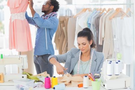 designer clothes: Fashion designer cutting textile at desk while her colleague adjusting dress behind