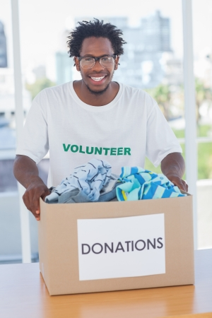 selfless: Happy man holding donation box with clothes