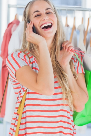 Blonde woman laughing in a clothing store while she is on the phone Stock Photo - 20592921