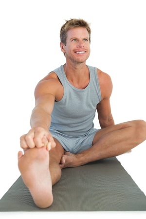 health fair: Man working out and stretching his leg on white background