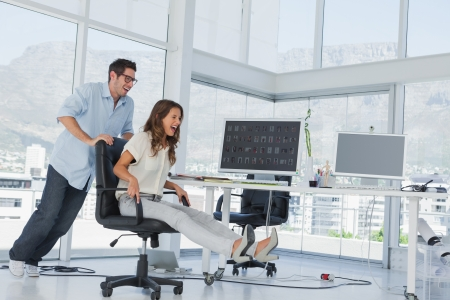Designers having fun with a swivel chair in their office photo