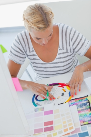 Interior designer working on a colour wheel at her desk with colour charts photo