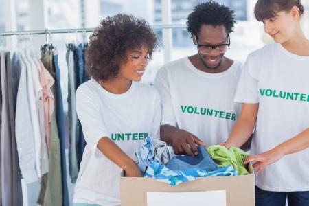 altruismo: Voluntarios alegres que toman la ropa de una caja de donaci�n en su oficina