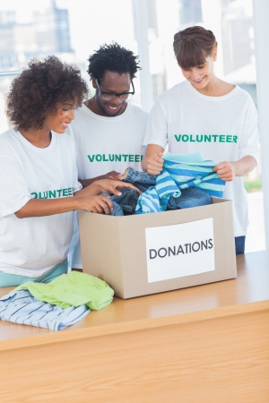 Cheerful volunteers looking at clothes from a donations box in their office photo