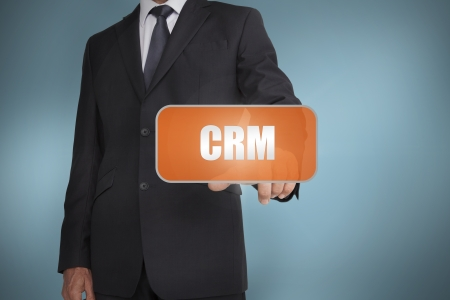 Businessman selecting orange tag with the word crm written on it on blue background photo