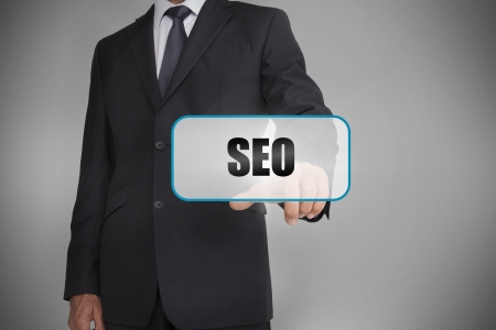 Businessman touching white tag with the word seo written on it on grey background photo